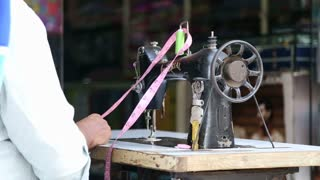 MUMBAI, INDIA - 7 JANUARY 2015: Man preparing to work on a sewing machine.