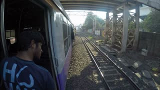 MUMBAI, INDIA - 7 JANUARY 2015: Man standing by open train door and watching landscape during ride.