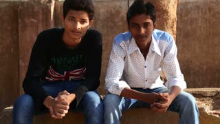 MUMBAI, INDIA - 7 JANUARY 2015: Portraits of two young Indian men sitting in park.