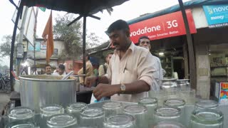 MUMBAI, INDIA - 7 JANUARY 2015: Timelapse of vendor preparing chai at street stand.
