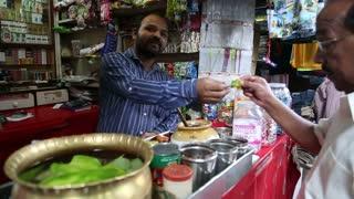 MUMBAI, INDIA - 8 JANUARY 2015: Indian man selling local food at a street stand in Mumbai.