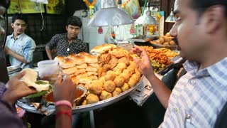 MUMBAI, INDIA - 8 JANUARY 2015: Indian men buying food and eating in front of a street food stand.