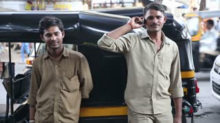 MUMBAI, INDIA - 8 JANUARY 2015: Indian men standing in front of a rickshaw on the street of Mumbai.