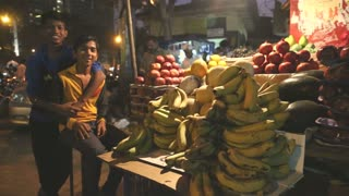 MUMBAI, INDIA - 8 JANUARY 2015: Indian teenage boys at a fruit stand of a busy street market.