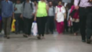 MUMBAI, INDIA - 8 JANUARY 2015: Legs of people walking through a busy train station in Mumbai, blurred.