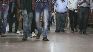 MUMBAI, INDIA - 8 JANUARY 2015: Legs of people walking through a busy train station in Mumbai.