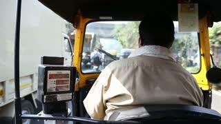 MUMBAI, INDIA - 8 JANUARY 2015: Local driver of ricksha during a ride in Mumbai, fast forwarded.