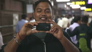 MUMBAI, INDIA - 8 JANUARY 2015: Portrait of an Indian man taking photo with a mobile phone.