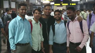 MUMBAI, INDIA - 8 JANUARY 2015: Portrait of five Indian men at a crowded train station in Mumbai.