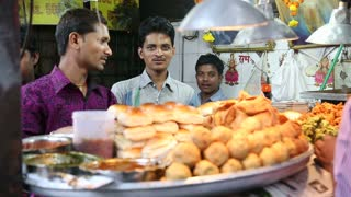 MUMBAI, INDIA - 8 JANUARY 2015: Portrait of young Indian men standing in front of a food stand.
