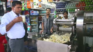 MUMBAI, INDIA - 8 JANUARY 2015: Vendor preparing food while Indian man drinks from a cup at shop in Mumbai.