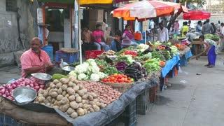MUMBAI, INDIA - 8 JANUARY 2015: Vendors selling vegetables at stands of a local market in Mumbai.