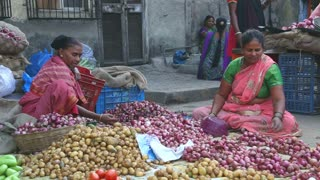 MUMBAI, INDIA - 8 JANUARY 2015: Women selling potatoes and onions at a local street market in Mumbai.