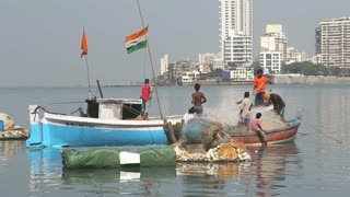 MUMBAI, INDIA - 9 JANUARY 2015: Children on a boat and people on the dock in a city bay of Mumbai.