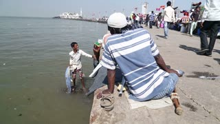 MUMBAI, INDIA - 9 JANUARY 2015: Family at the dock of the bay and people passing by in the background.