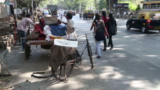 MUMBAI, INDIA - 9 JANUARY 2015: Man placing a large ice cube on a bike at the street of Mumbai.