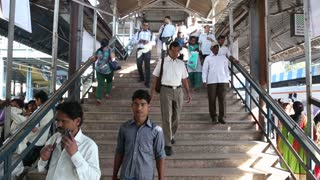 MUMBAI, INDIA - 9 JANUARY 2015: People walking down the stairs towards the train station in Mumbai.