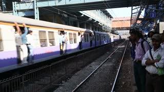 MUMBAI, INDIA - 9 JANUARY 2015: Train full of people passing through the train station in Mumbai.