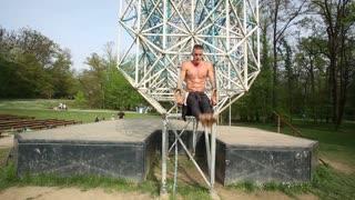 Muscular man doing pull-ups on gymnastics rings