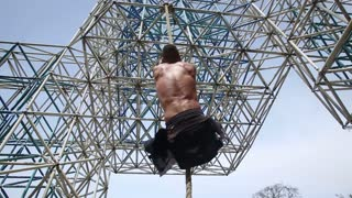 Muscular man is climbing on the rope