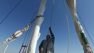 NILE, EGYPT - FEBRUARY 8, 2016: Local crew member raising sail on felucca boat