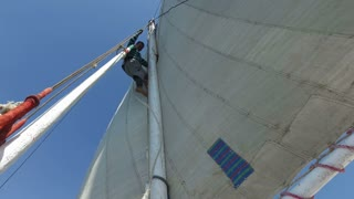 NILE, EGYPT - FEBRUARY 8, 2016: Nubian felucca sailing crew tying rope on felucca sail