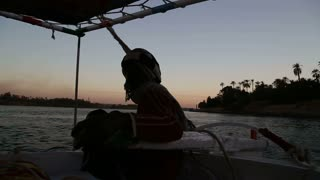 Nubian man sailing with felucca on the Nile in the evening