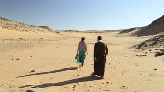 Nubian man walking with female tourist in desert