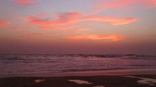 Ocean view in Hikkaduwa in sunset with waves splashing the beach.