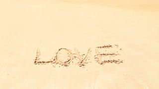 Ocean wave approaching word love written in sand on beach