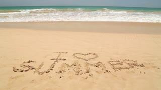 Ocean wave approaching words I love summer written in sand on beach