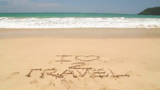Ocean wave approaching words I love to travel written in sand on beach