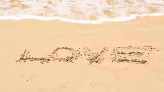 Ocean wave covering word love written in sand on beach