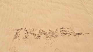 Ocean wave covering word travel written in sand on beach