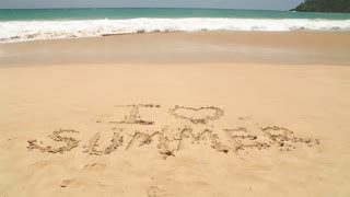Ocean wave covering words I love summer written in sand on beach