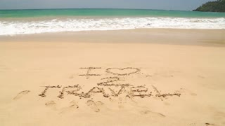 Ocean wave covering words I love to travel written in sand on beach