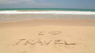 Ocean wave covering words I love travel written in sand on beach