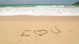 Ocean wave covering words I love you written in sand on beach