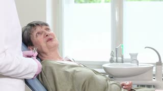 Old woman sitting in dental chair and having routine dental checkup