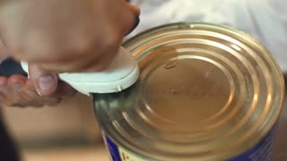 Opening a can of tomato sauce