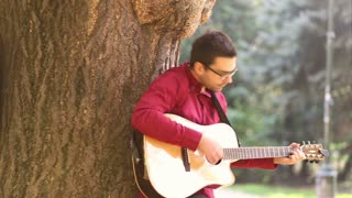 Pan shot of young couple playing guitar and singing while leaning against tree in park, graded