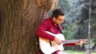 Pan shot of young couple playing guitar and singing while leaning against tree in park