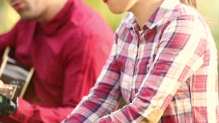 Panoramic view of beautiful young couple playing guitar and singing while sitting on park bench, graded