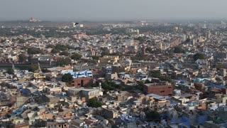 Panoramic view of Jodhpur cityscape, with dog watching from a wall.