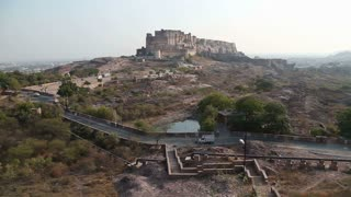 Panoramic view of Mehrangarh fort, with roadside and cityscape in background.