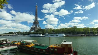 PARIS - OCTOBER 2012: Timelapse of boats on seine river and eiffel tower on October 12, 2012 in Paris, France. The Eiffel Tower is the most visited tourist attraction in Paris.