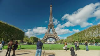 PARIS - OCTOBER 2012: Timelapse of crowds infront of Eiffel Tower with clouds passing by October 12, 2012 in Paris, France. The Eiffel Tower is the most visited tourist attraction in Paris.