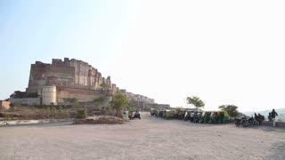 Parking lot with rickshaws beneath Mehrangarh fort in Jodhpur.