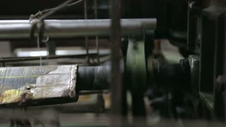 Part of weaving machine moving fast during work.