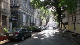 Peaceful suburban street in Mumbai, with cars and apartment buildings.